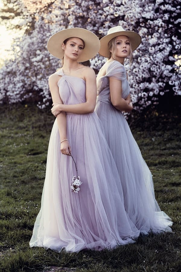 bridesmaids in light purple dresses in a garden wearing natural makeup