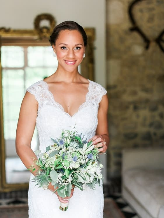 Bride wearing lace wedding dress and holding a flower bouquet natural bridal makeup look for darker skin
