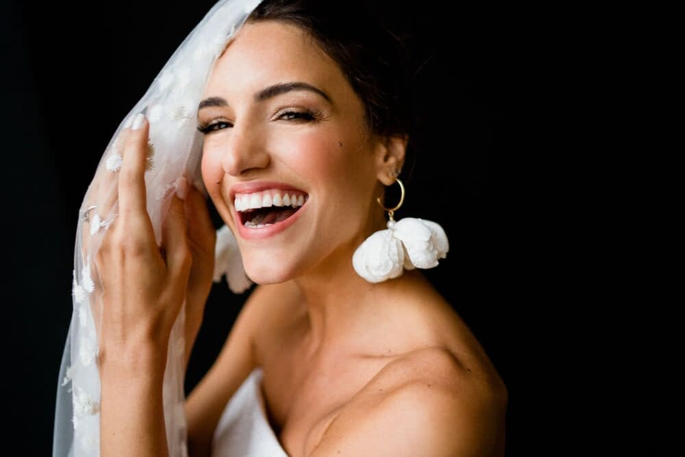White modern bridal earrings laughing bride natural wedding makeup look