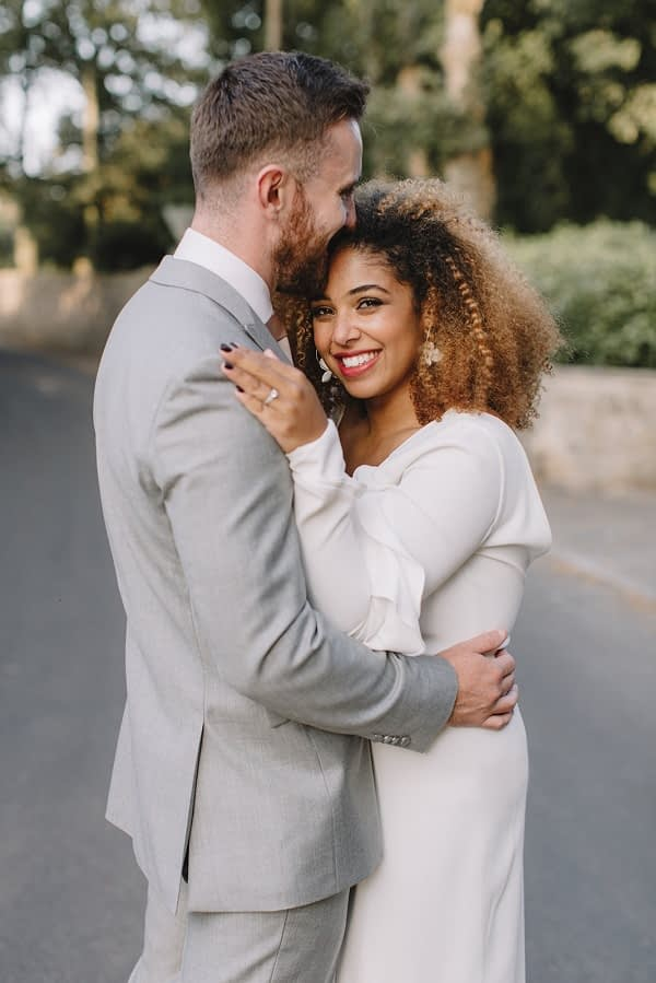 Bride and groom embracing themselves bride with naturally curly hair wearing natural makeup with red lips