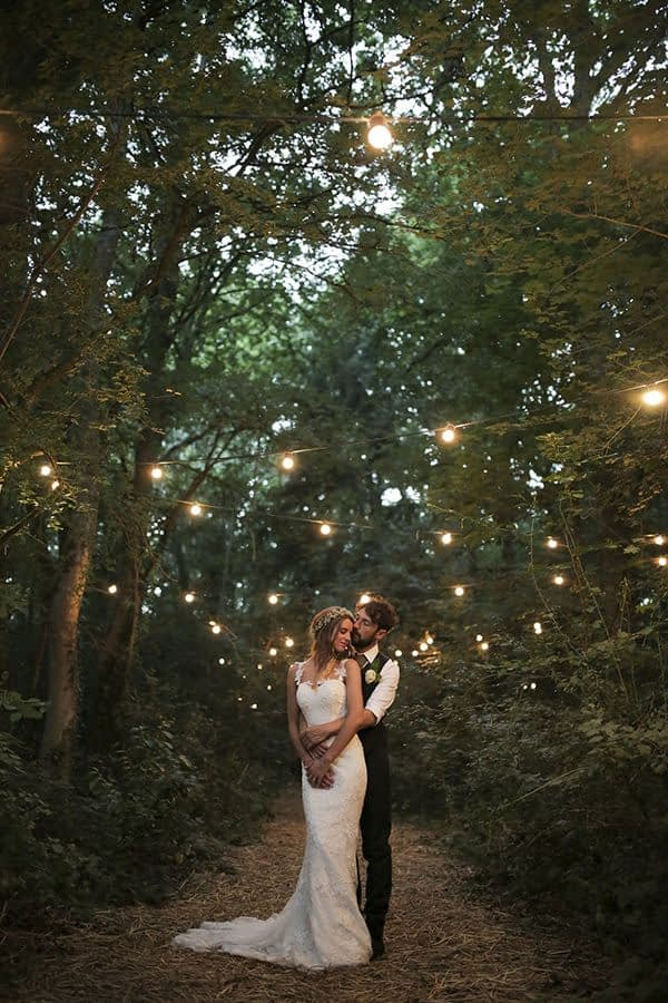 Just married couple in a wood surrounded by the fairy lights. Natural bridal beauty
