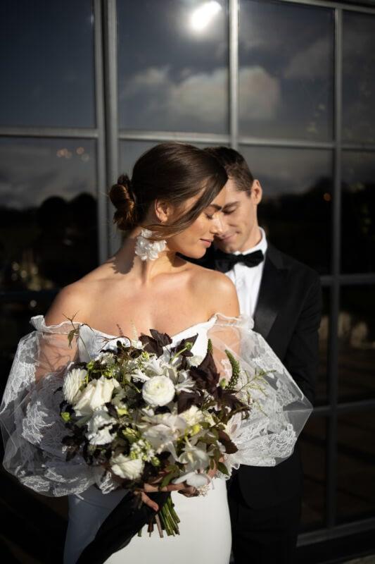 Bride wearing off shoulders wedding dress, hair pined up glowing skin natural makeup look