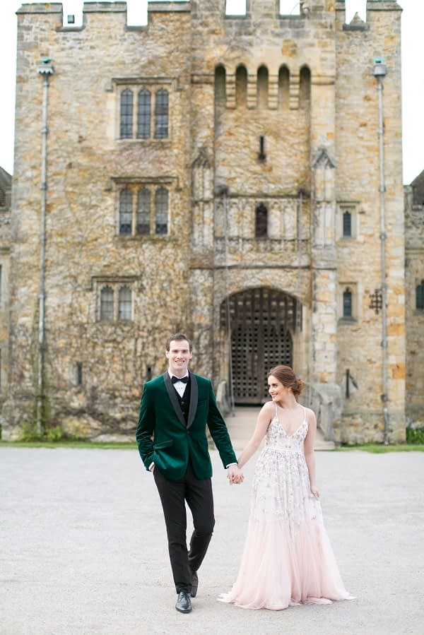 Bride and groom in front of the Hever castle Bride wearing pink blush wedding dress groom wearing a bottle green velvet tuxedo
