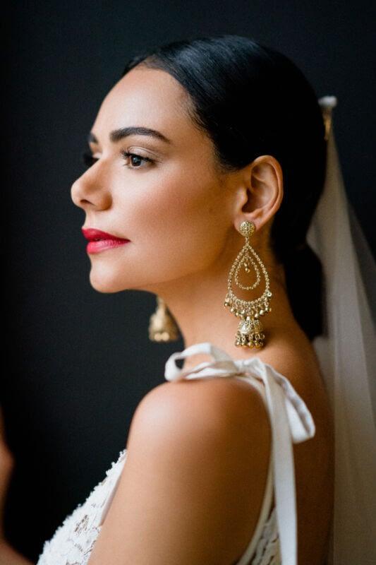 Flawless wedding makeup with red lips Brazilian beauty wearing gold earrings