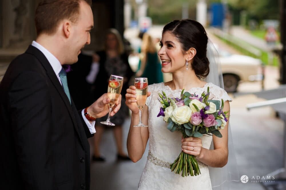 Soft and natural birdal amkeup look bride and groom drinking champagne after ceremony