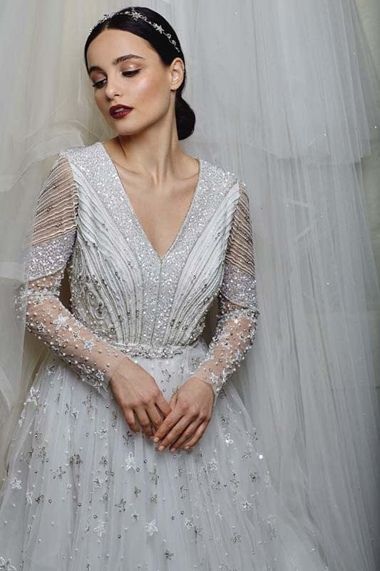 Bridal makeup with deep red lips wearing wedding dress with long sleeves