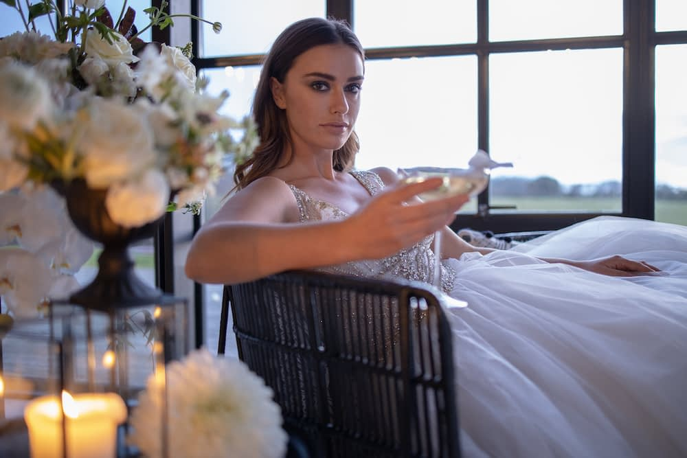 Glamourous wedding dress bride drinking champagne modern bridal makeup with nude lips