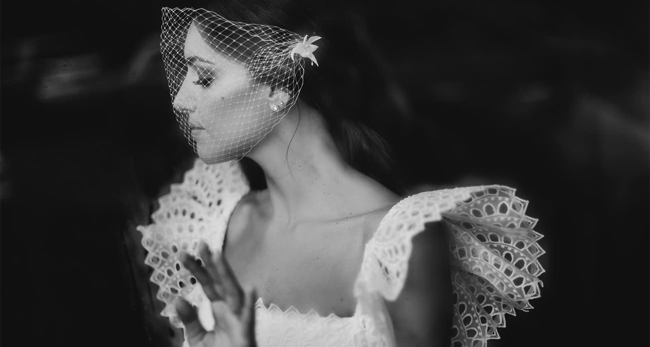 Bride wearing birdcage veil wedding headpiece and soft natural modern makeup