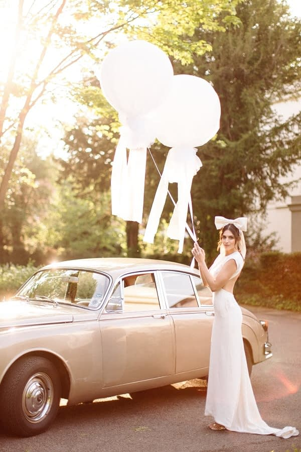 Bride standing next to a wedding car. Modern wedding dress minimal makeup look hair bow