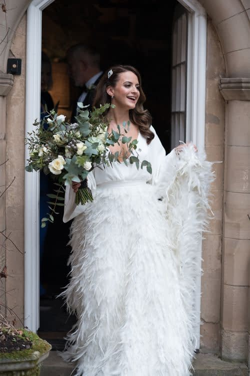 ostrich Bride wearing feather skirt wedding dress leaving the venue