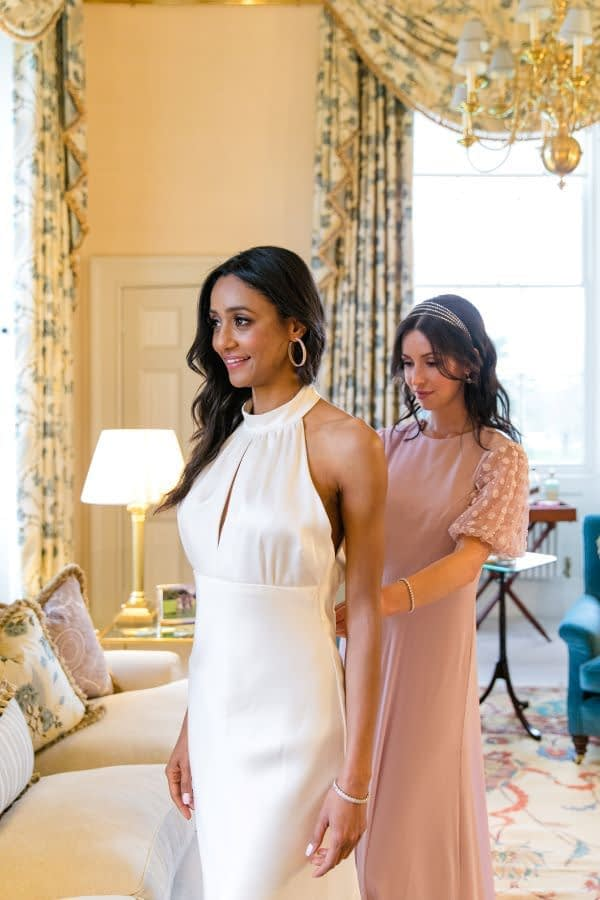 Bride getting ready with the bridesmaid wearing silk backless white wedding dress natural glowing makeup for Indian bride